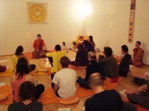 Eine Gruppe von Akhanda Kirtan Praktizierenden, am Boden sitzend.